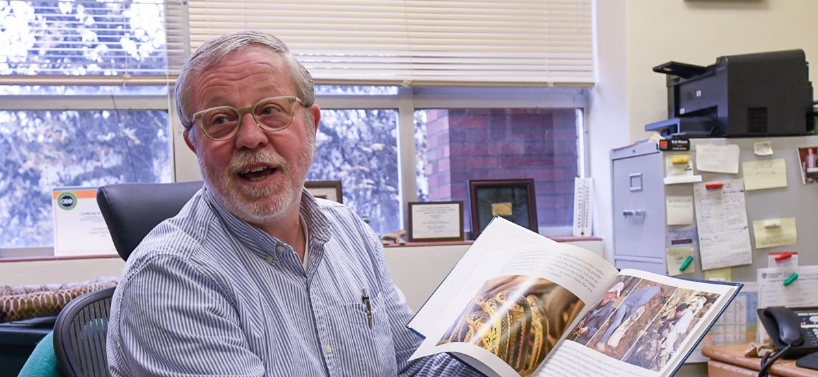 photo of Bob Mason showing a book about snakes