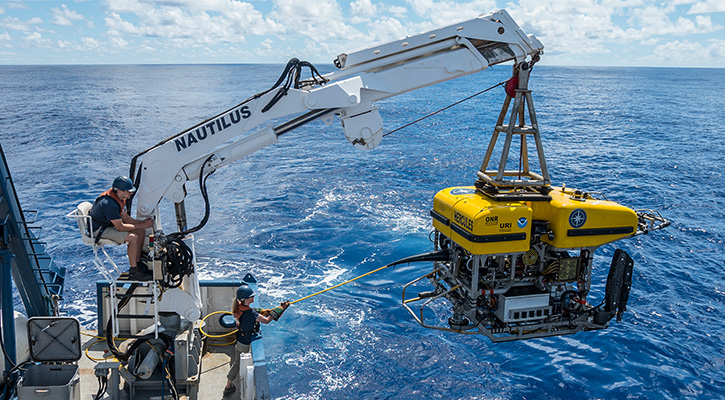 photo of scientific equipment being lowered into ocean