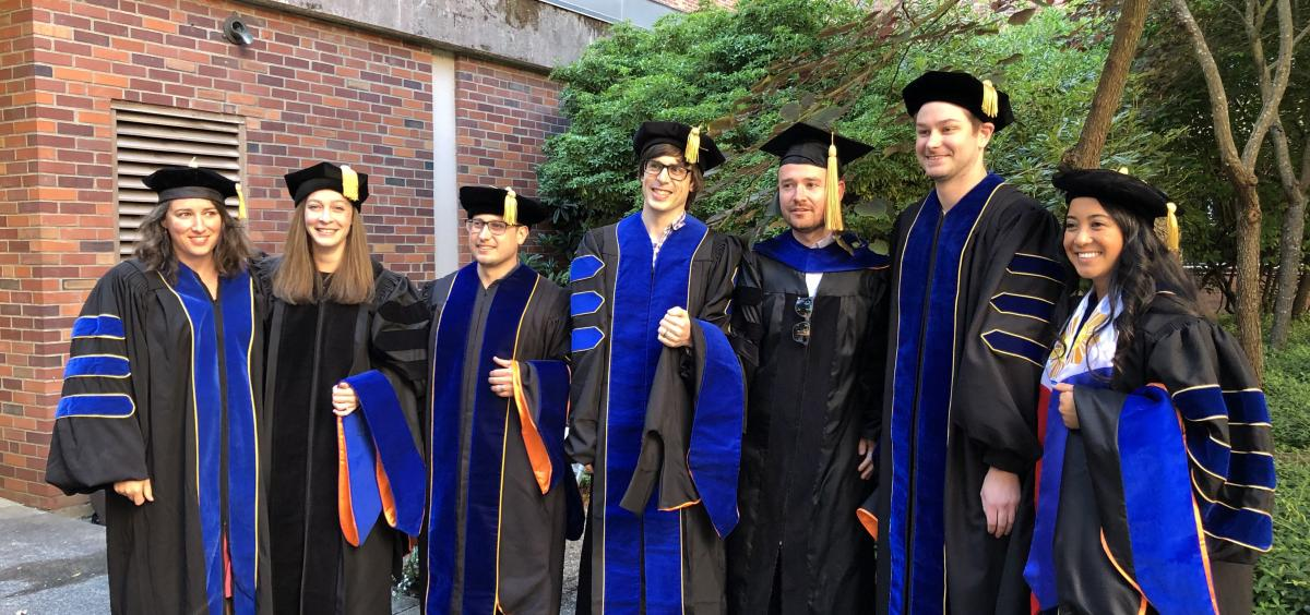 Seven IB graduate students in commencement regalia