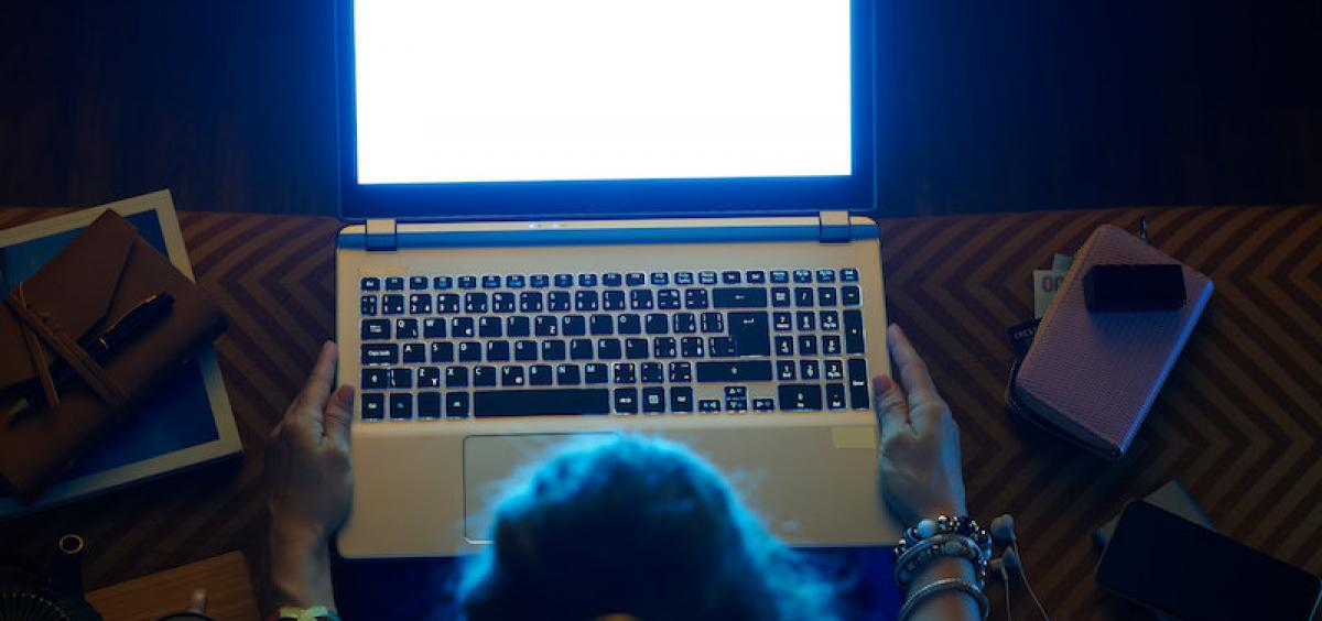 photo of a woman looking at blue light from a computer screen