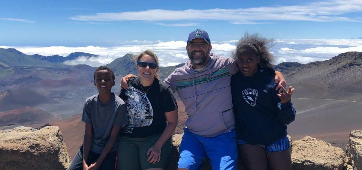 Dee Denver and his family with mountains in background
