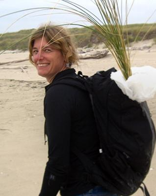 Sally Hacker on beach with pack of grass on her back