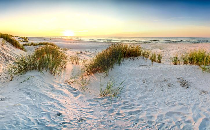 sand dune with sun setting over ocean