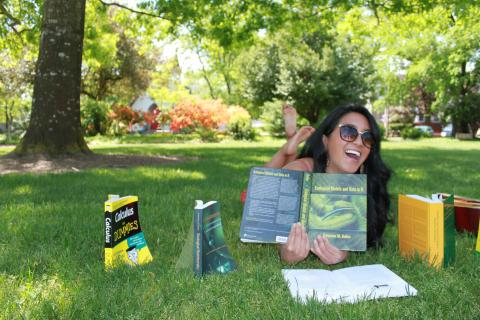 picture of Leah Segui on the grass, surrounded by books